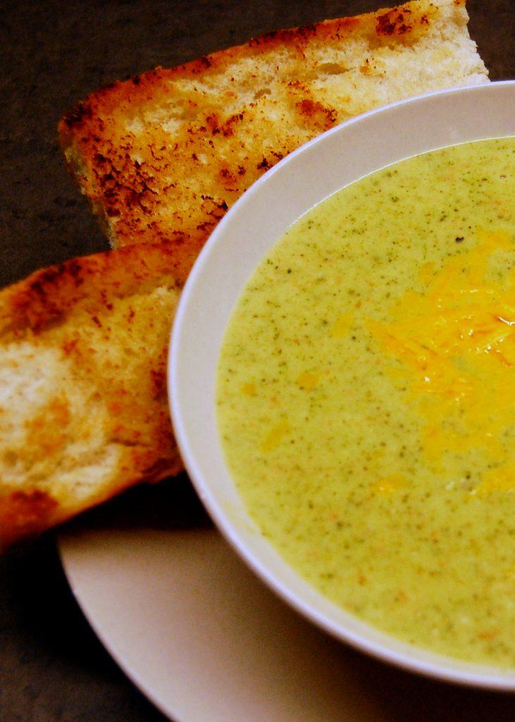 bowl of broccoli cheddar soup with garlic bread