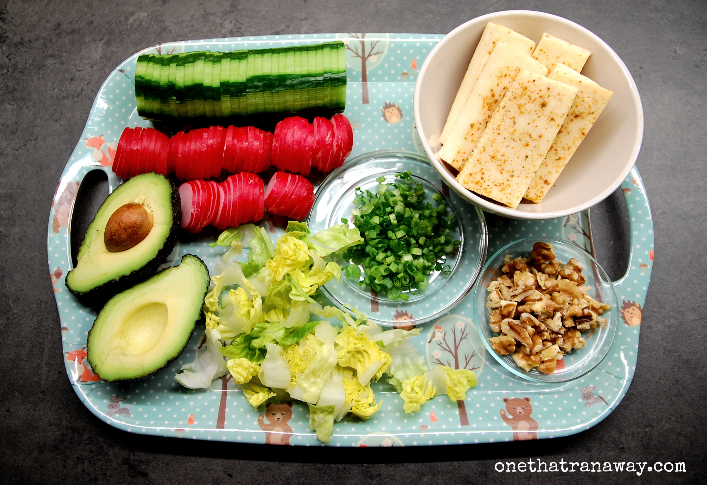 cucumber, red radishes, avocado, walnuts and halloumi cheese on a tray