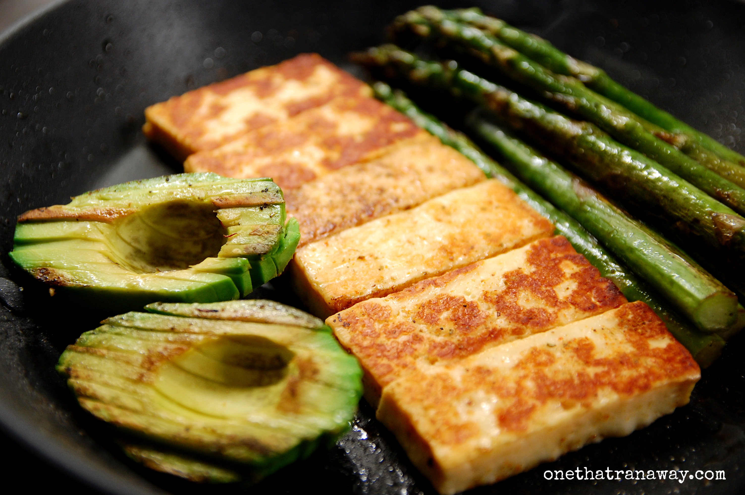 fried halloumi cheese, asparagus and avocado in a pan