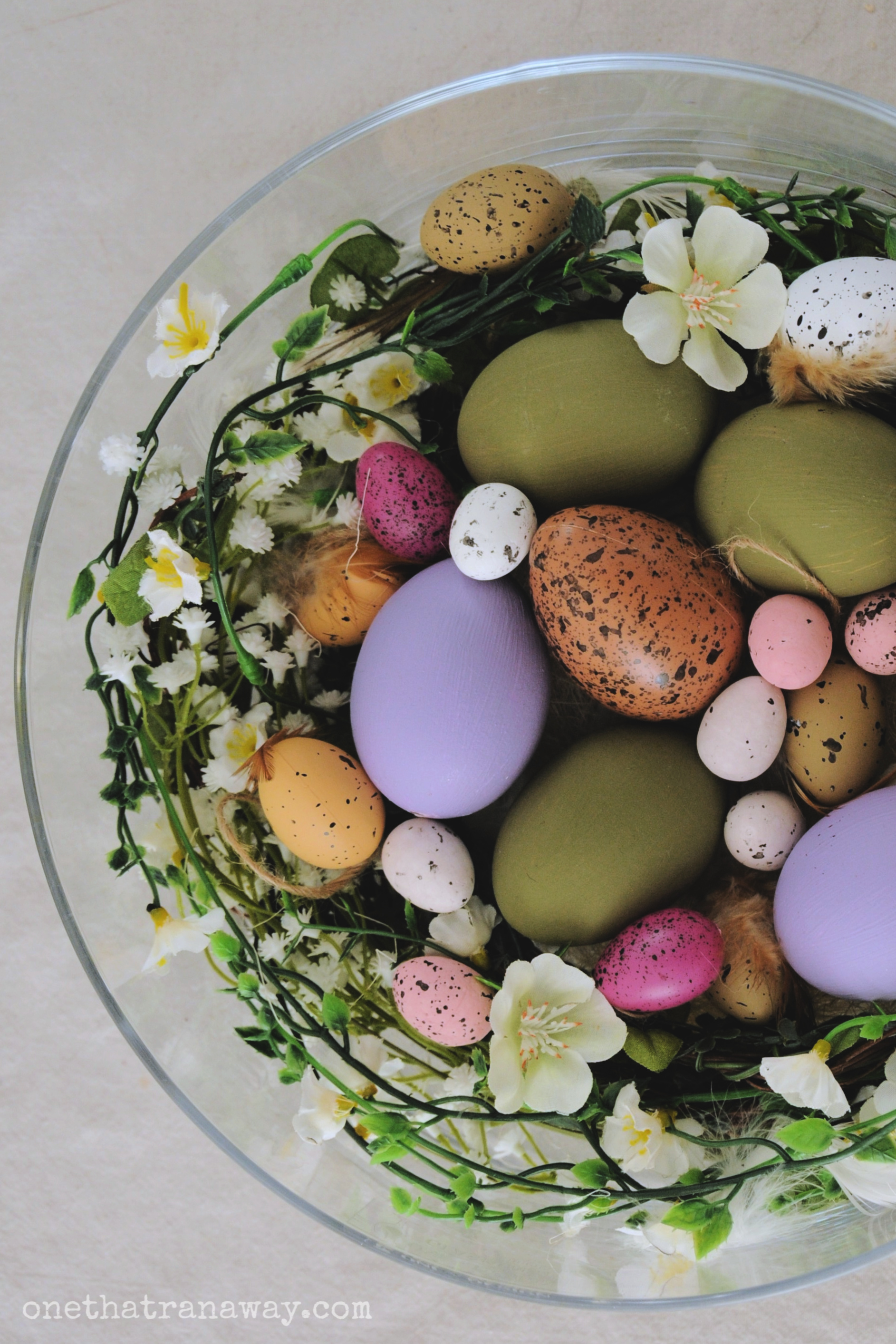 easter nest in a bowl with flowers and feathers
