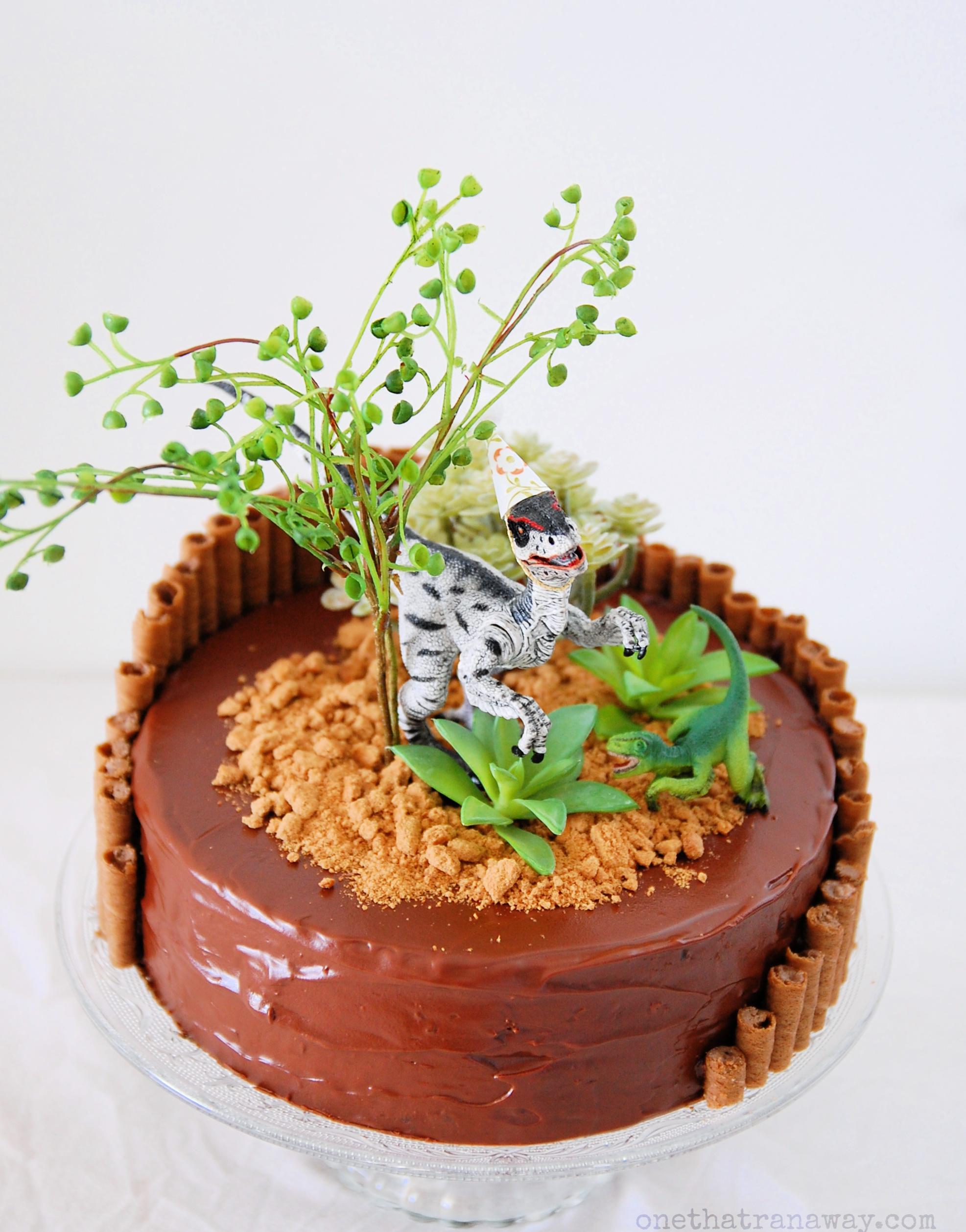 toy dinosaur on chocolate cake
