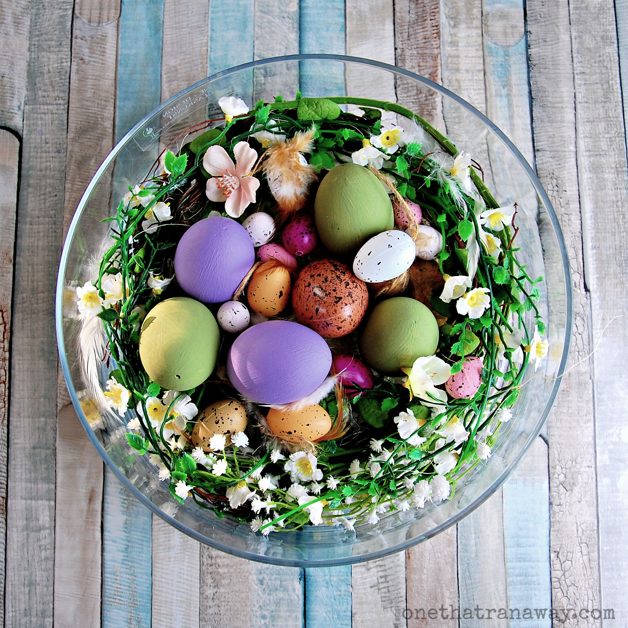easter nest with speckled and hand-painted eggs on a vintage wooden surface