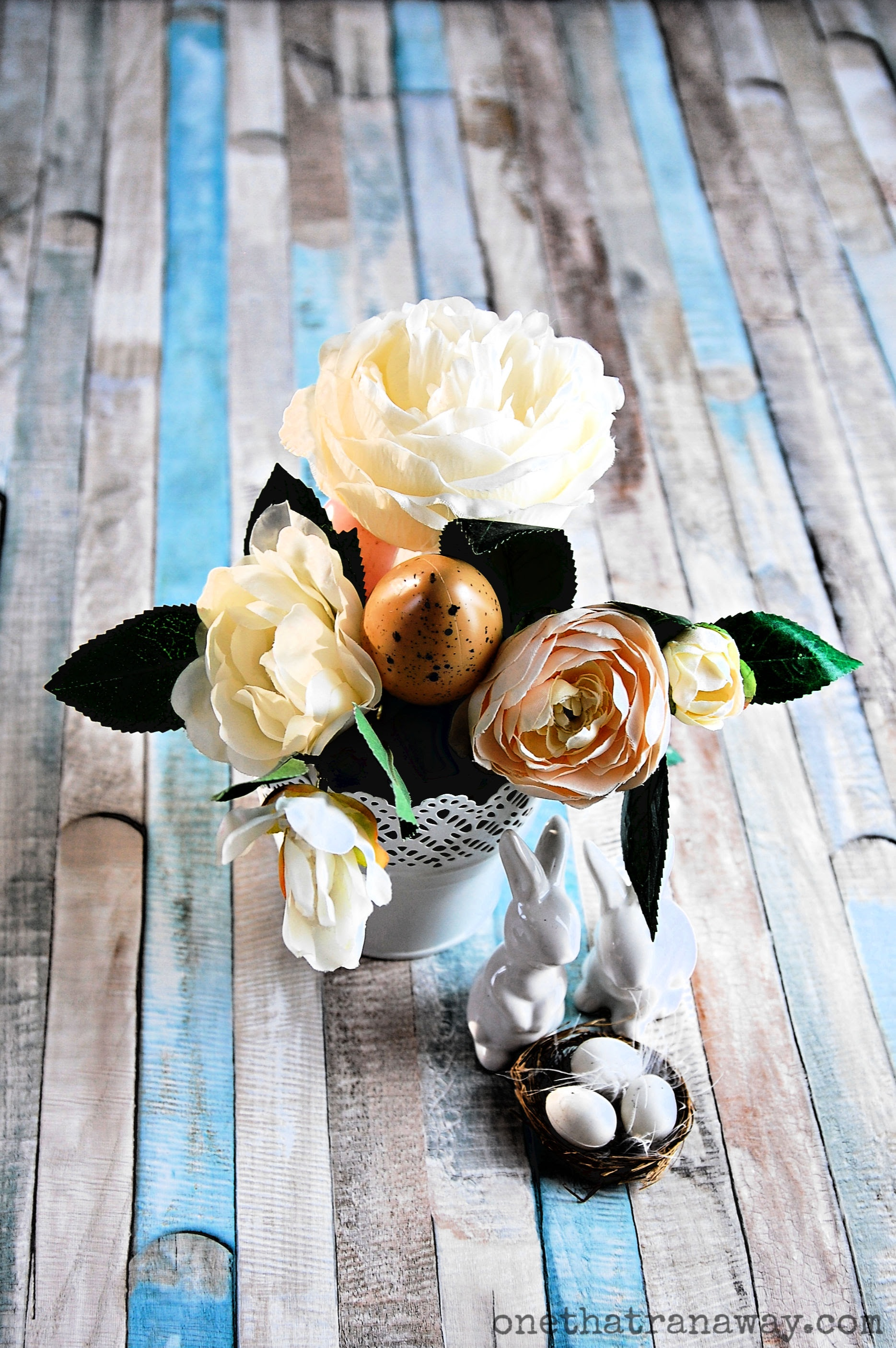 flower bouquet with easter eggs and porcelain easter bunnies on a wooden surface