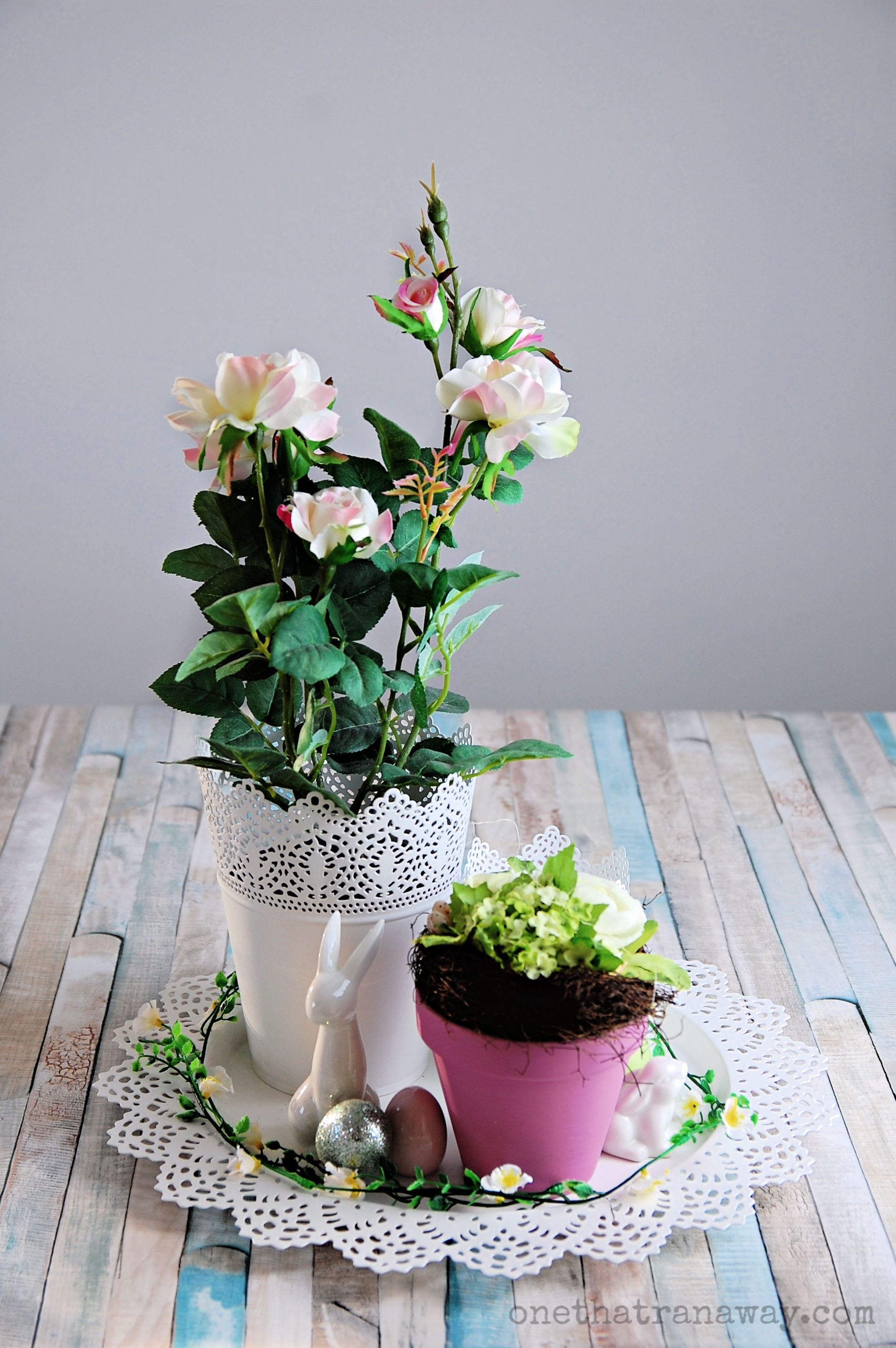 easter decorations with a flower bouquet, a white ceramic bunny and rose flowers
